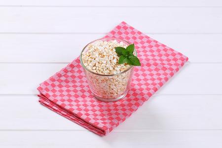 glass of puffed buckwheat on checkered place mat