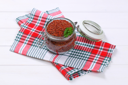 jar of red rice on checkered place mat Banco de Imagens