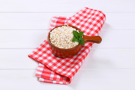saucepan of puffed buckwheat on checkered place mat