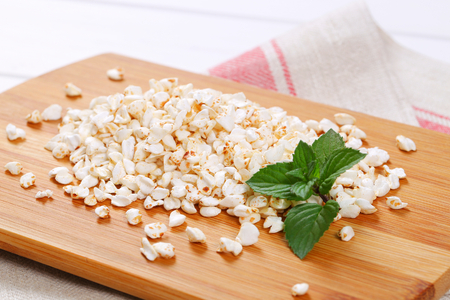 pile of puffed buckwheat on wooden cutting board - close up Stock Photo
