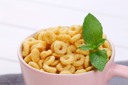 mug of honey cereal rings on grey place mat - close up