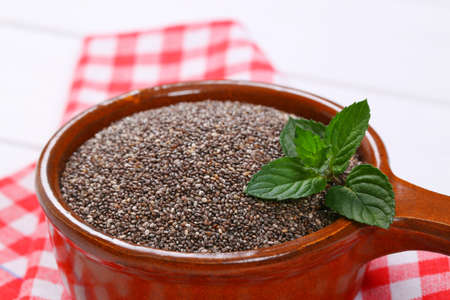 saucepan of chia seeds on checkered place mat - close up Stock Photo