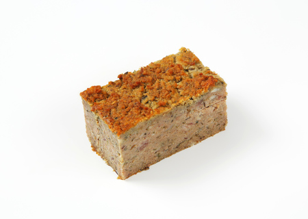 piece of oven-baked pork and liver meatloaf on white background