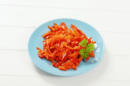 plate of pickled red peppers on white wooden background