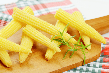 stack of sweet baby corn on wooden cutting board - close up