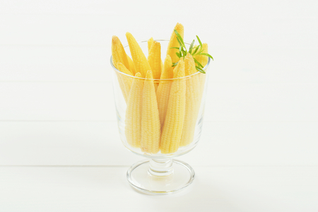 glass of sweet baby corn on white wooden background Banco de Imagens