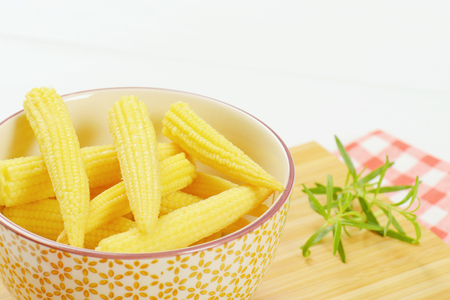 bowl of sweet baby corn on wooden cutting board - close up