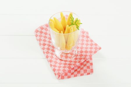 glass of sweet baby corn on checkered place mat Banco de Imagens