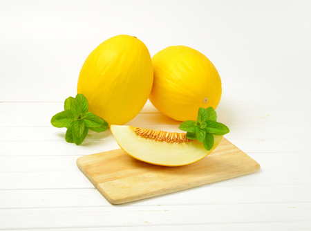 two whole yellow melons and slice of melon next to them on cutting board Reklamní fotografie