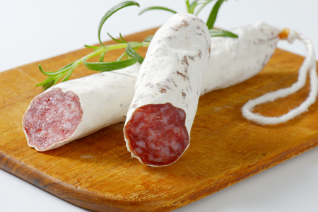 Spanish thin dried sausage on cutting board