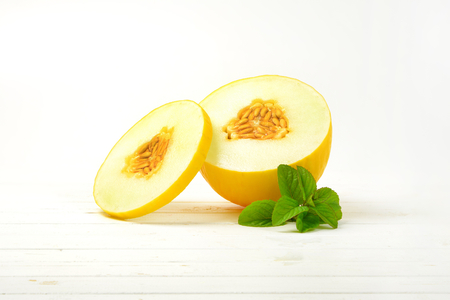 half and slice of yellow melon on white wooden background