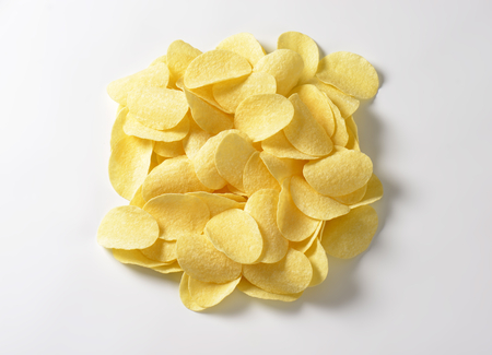 Thin salted potato chips (crisps) on white background