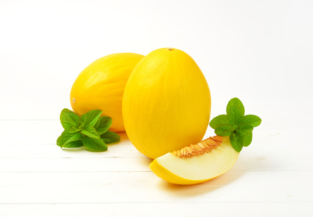 fresh yellow melons on white wooden background
