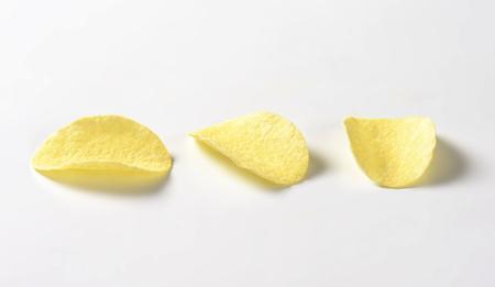 Three thin salted potato chips (crisps) on white background