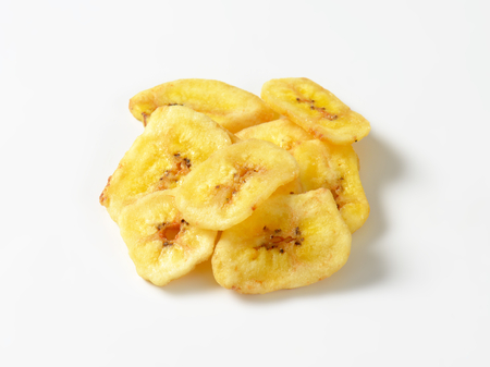 Heap of dried thin banana slices on white background