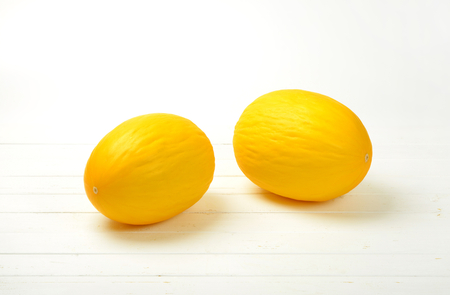 two whole yellow melons on white wooden background Reklamní fotografie