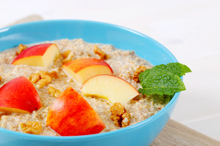 bowl of oatmeal porridge with apples and walnuts on beige place mat - close up Фото со стока