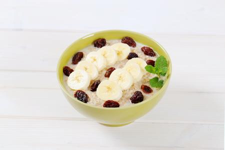 bowl of oatmeal porridge with banana and raisins on white background Stok Fotoğraf