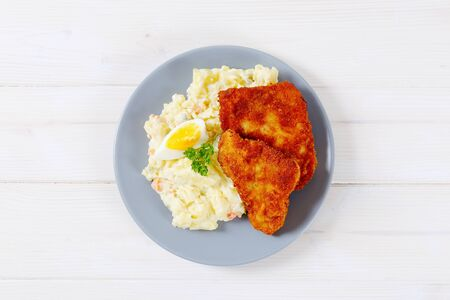 breaded schnitzels with potato salad on grey plate 版權商用圖片