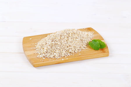 dry rolled oatmeal on wooden cutting board