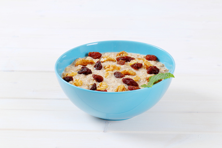 bowl of oatmeal porridge with raisins and walnuts on white background