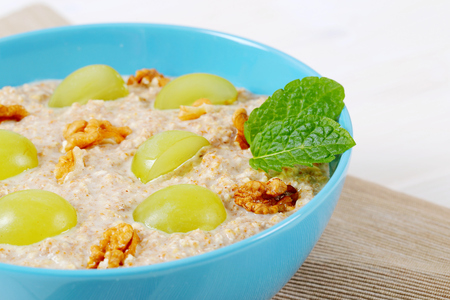 bowl of oatmeal porridge with grapes and walnuts on beige place mat - close up
