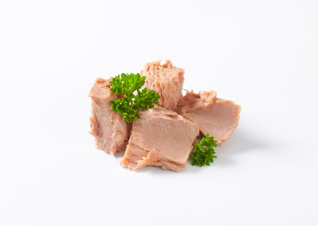 pieces of canned tuna with parsley on white background