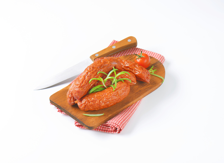 Lightly smoked and dried kielbasa sausages on cutting board Stock Photo