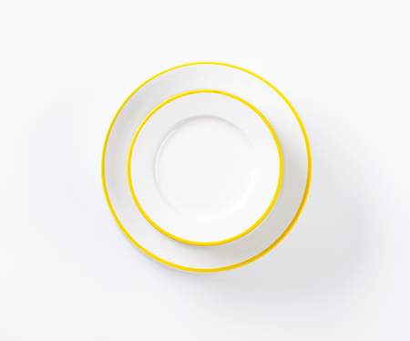 two white plates with yellow rim on white background
