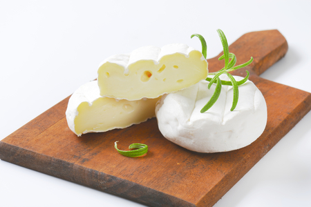 soft cheese with white rind on wooden cutting board - close up
