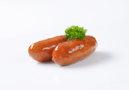 two grilled short sausages with parsley on white background