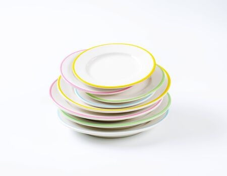 stack of rimmed plates on white background
