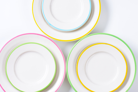 set of white plates with colorful rims on white background