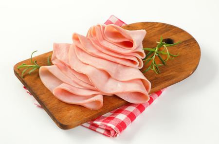 thin slices of ham and fresh rosemary leaves on wooden cutting board Stock Photo - 97296752