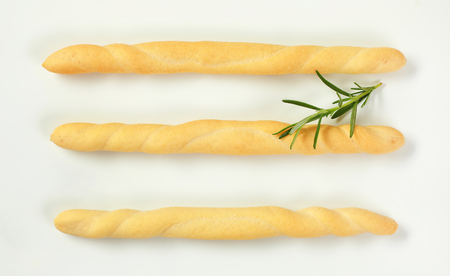 three crispy bread sticks and rosemary on white background