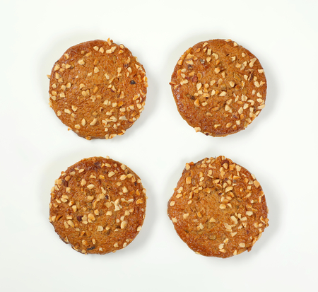 four cookies with chopped nuts and almonds on white background