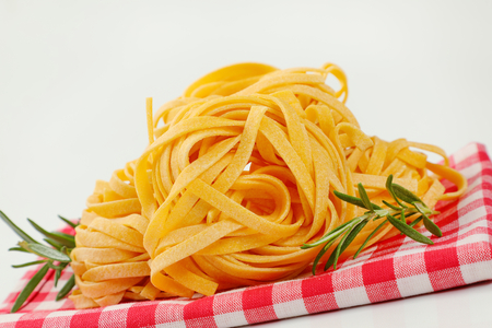 bundles of dried ribbon pasta on checkered place mat - close up Stock Photo