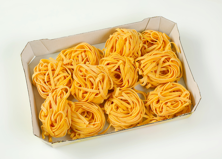box of dried ribbon pasta bundles on white background Banco de Imagens