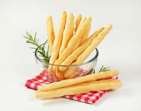 bowl of crispy bread sticks on checkered place mat Stock Photo