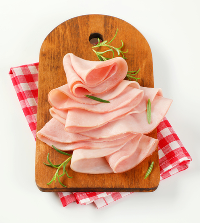 thin slices of ham and fresh rosemary leaves on wooden cutting board