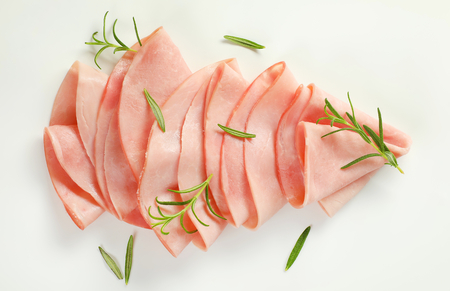 thin slices of ham with fresh rosemary leaves on white background