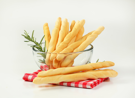 bowl of crispy bread sticks on checkered place mat Stock Photo