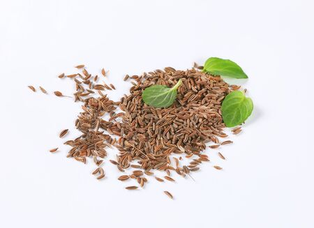 handful of caraway seeds on white background