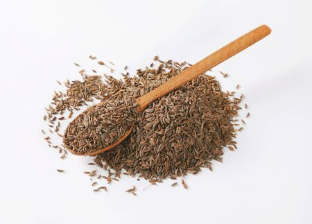 pile and spoon of caraway seeds on white background