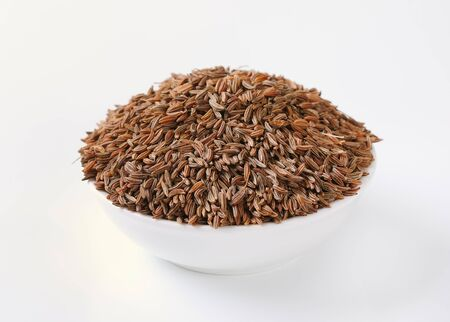 bowl of caraway seeds on white background