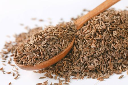 pile and spoon of caraway seeds - close up