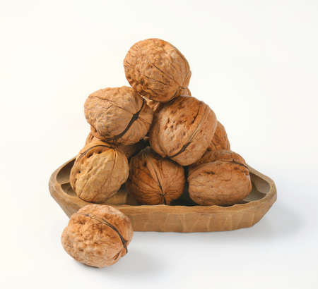 bowl of whole walnuts on white background
