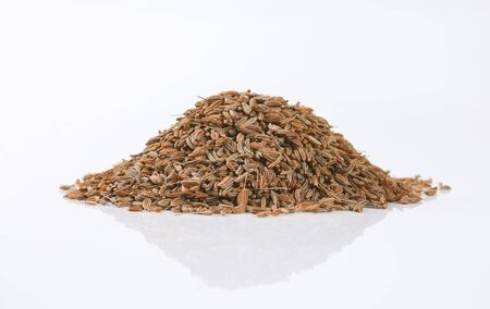 pile of caraway seeds on white background