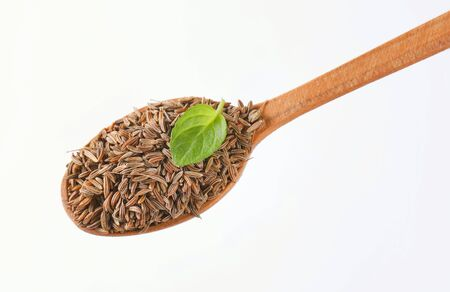 spoon of caraway seeds on white background