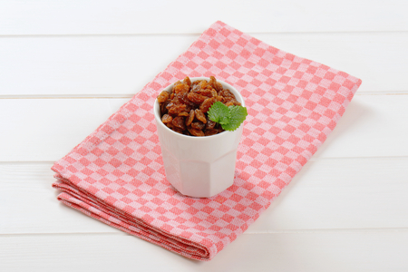 cup of sweet raisins on checkered place mat